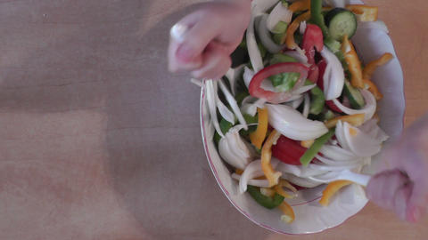 Pair of child hands mixing a colorful salad on the Footage