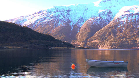 Small boat floating on crystal clear waters of a glacial fjord Footage