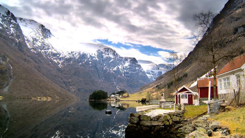 Time-lapse clouds over remote homes beside a glacial fjord Footage