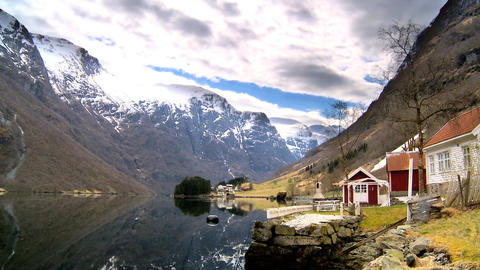 Time-lapse clouds over remote homes beside a glacial fjord Stock Video Footage