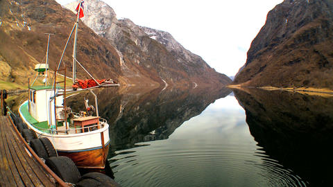 Fishing boat moored on mirror clear water of glacial fjord Stock Video Footage