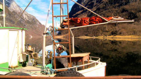 Fishing boat moored on mirror clear water of glacial fjord Footage