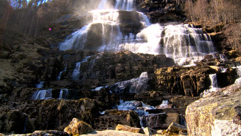 Cascading waters of a powerful waterfall crashing onto rocks Stock Video Footage