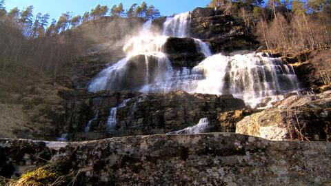 Cascading waters of a powerful waterfall crashing onto rocks Footage
