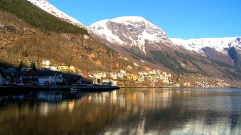 Small hillside community beside the crystal waters of a glacial fjord Footage