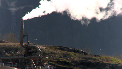 Oil refinery smoke polluting the air in a glacial valley Footage