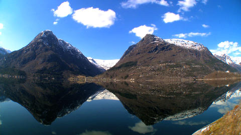Time-lapse clouds over crystal waters of a glacial fjord Stock Video Footage