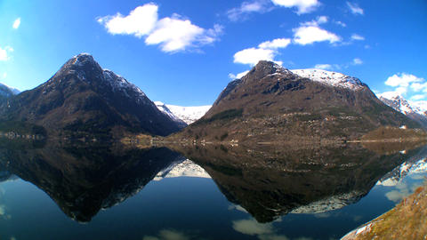 Time-lapse clouds over crystal waters of a glacial fjord Footage