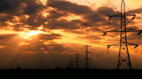 Time-lapse clouds at sunset over electricity pylons Stock Video Footage