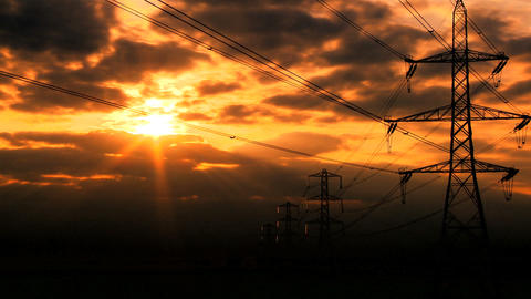 Time-lapse clouds at sunset over electricity pylons Footage