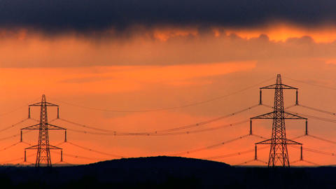 Time-lapse dark clouds at sunset over electricity pylons Footage