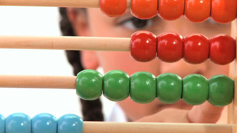 Cute african american schoolgirl early learning counting with an abacus Footage
