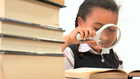 Cute african american schoolgirl using a spy glass with a book Footage