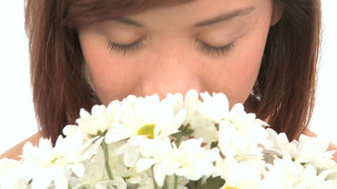 Young western oriental girl enjoying the therapeutic aroma of flowers Footage