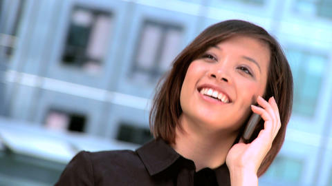 Ambitious young city businesswoman talking on a mobile(cell) phone 影片素材
