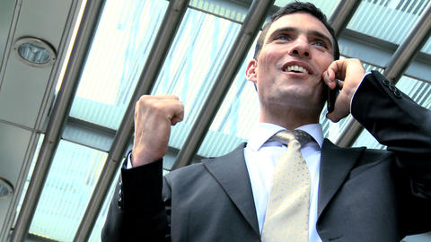Ambitious young city businessman celebrating good news on a mobile(cell) phone Footage