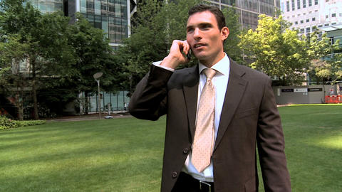Smart young city business man talking on mobile(cell) phone (Steadicam) Footage