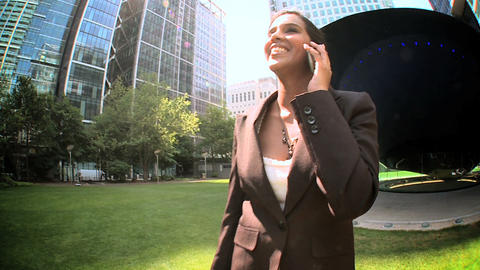 Young city business woman talking on mobile(cell) phone outdoors(Steadicam) Footage