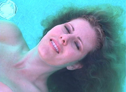 Beautiful Blonde Floating in a Pool-1 Stock Video Footage