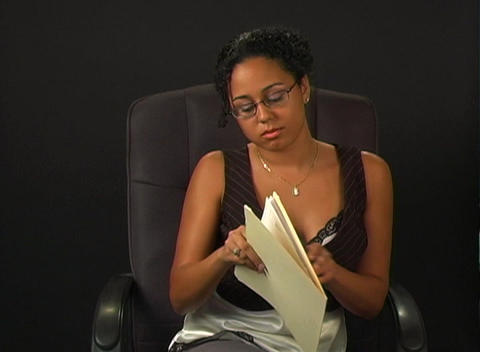 Beautiful Young Woman in an Office Chair with a File Folder Stock Video Footage