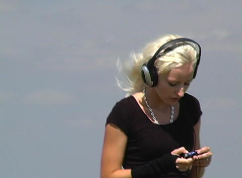 Beautiful Blonde with Headphones Outdoors Stock Video Footage