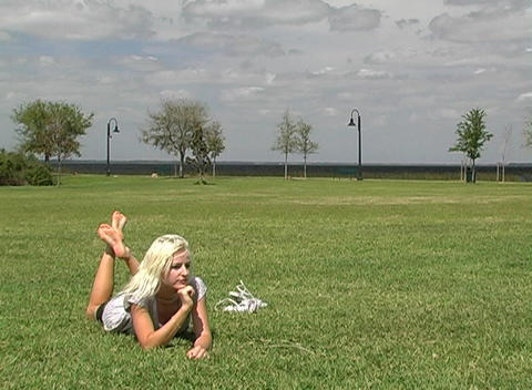 Beautiful Blonde Relaxes at Lakefront Park Footage