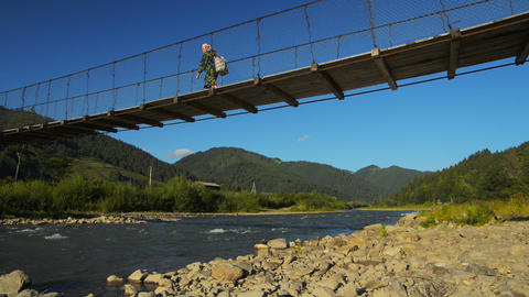 Suspension bridge across mountain river Stock Video Footage