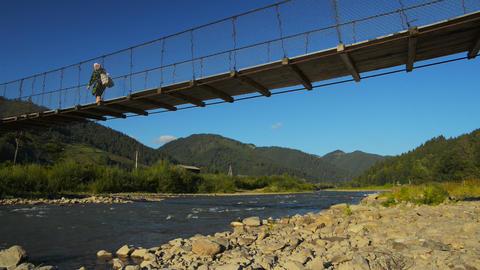 Suspension bridge across mountain river Footage