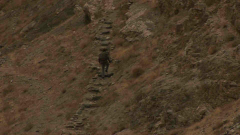 Guy climbing stairs rocks Tajikistan Stock Video Footage