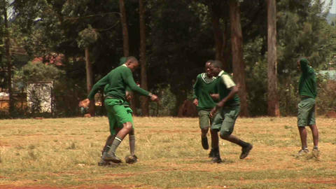 Kids playing soccer on dusty road Stock Video Footage