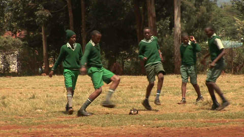 Kids playing soccer on dusty road Footage