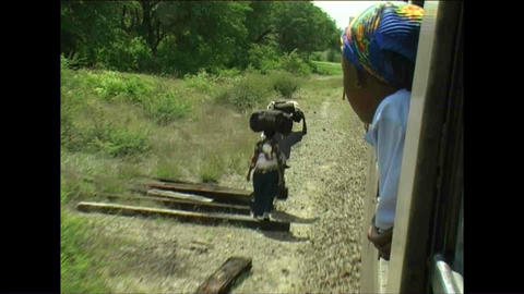 People walking next to train Woman watching Zimbab Stock Video Footage