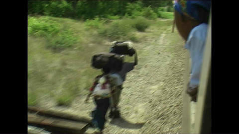 People walking next to train Woman watching Zimbab Stock Video Footage
