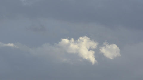 White cloud moving in front of dark clouds Stock Video Footage