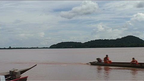 Monks in longboat passing by Stock Video Footage