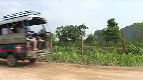 Vang Vieng tuktuk passing by Stock Video Footage