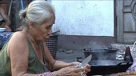 Luang Prabang, woman makes food on the street Stock Video Footage