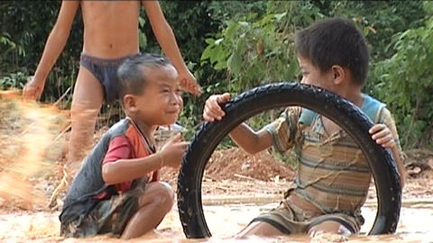 Children playing with wheels in water Footage