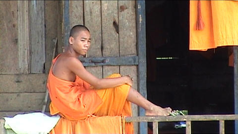 Monk on porch of house Footage