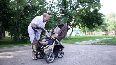 Granny playing with her grandson in the yard Stock Video Footage