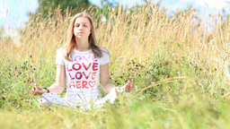 Young girl in white meditating in the city park Footage