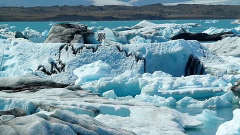 Icebergs float in a vast blue glacier lagoon in th Footage