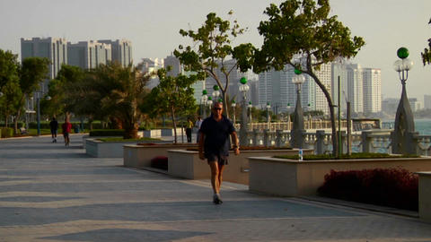 Joggers run beside the beautiful skyline of Abu Dh Stock Video Footage