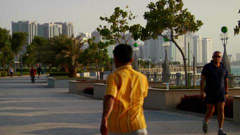 Joggers run beside the beautiful skyline of Abu Dh Footage