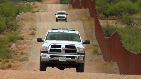 Border patrol vehicles move along the U.S. Mexico  Footage