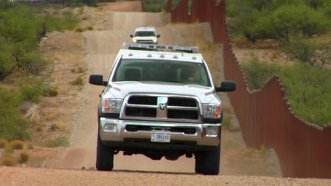 Border patrol vehicles move along the U.S. Mexico Stock Video Footage
