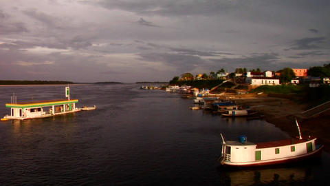Boats move along the Amazon River near a village Stock Video Footage