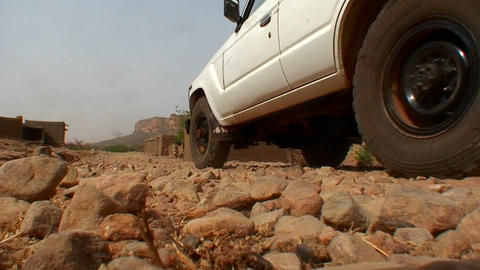 A UN type jeep drives down a stone covered road in Live Action