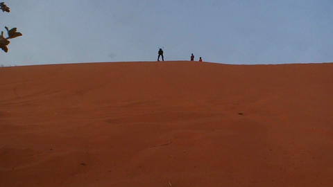 People practice the odd sport of skiing on desert Stock Video Footage