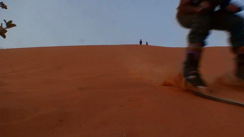 People practice the odd sport of skiing on desert Stock Video Footage